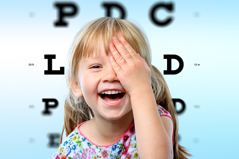 young child smiling during eye exam